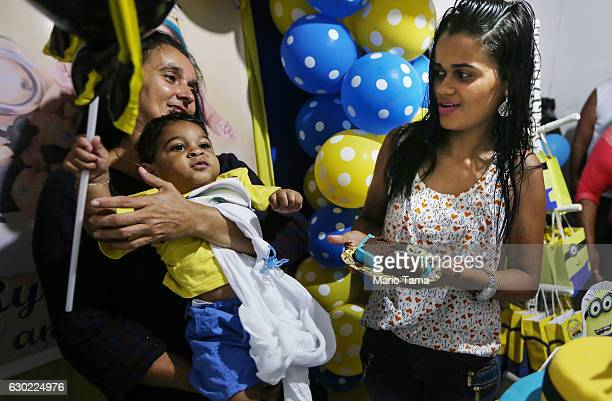 Ryquelme Kauan who was born with microcephaly is held by his grandmother Valeria as his mother Avila serves cake at his one year birthday party on...