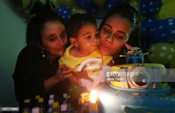 Ryquelme Kauan who was born with microcephaly is held by his grandmother Valeria and mother Avila as they blow out the candle at his one year...
