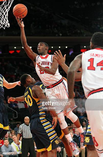 Rysheed Jordan of the St John's Red Storm puts the ball up to the basket against Deonte Burton of the Marquette Golden Eagles during the game at...