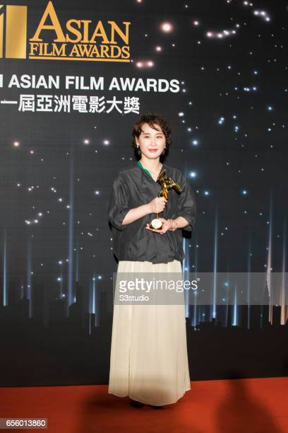 Ryu Seong-hie, winner of the Best Production Design award for 'The Handmaiden', poses with the award during the 11th Asian Film Awards on March 21,...