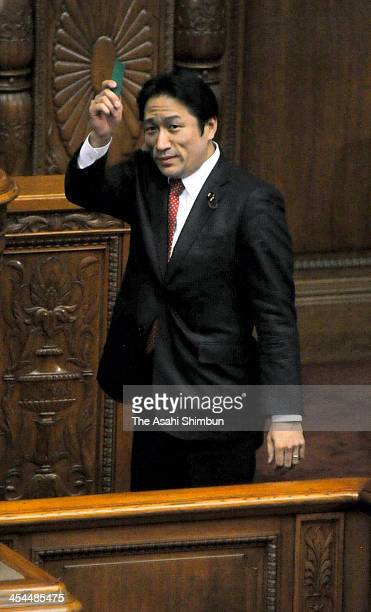 Ryuhei Kawada Upper House member of Your Party holds a blue ballot to vote against the party policy at the diet building on December 6 2013 in Tokyo...
