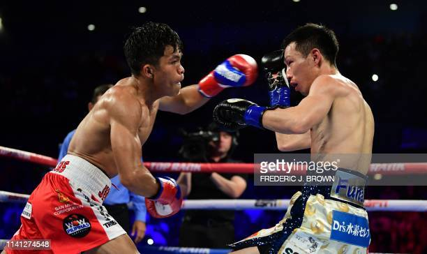 Ryuichi Funai of Japan reacts to a left hook by Jerwin Ancajas of the Philippines during their 12round Super Flyweight IBF World Title fight in...