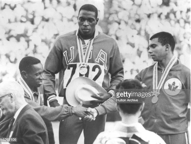 ON THE ROSTRUM AFTER RECEIVING HIS GOLD MEDAL FOR WINNING THE MEN's 100 METRE FINAL AT THE OLYMPIC GAMES IN TOKYO WATCHES SILVER MEDAL WINNER ENRIQUE...