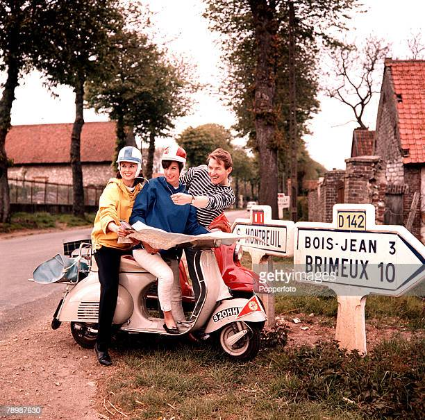 1960's A couple astride a Vespa motorscooter ask for directions whilst touring France