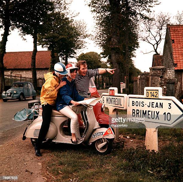 S, A couple astride a Vespa motorscooter ask for directions whilst touring France