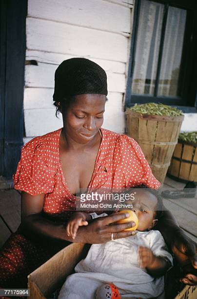 MID 1930's A slave woman and her baby sit on the porch of their house during a recreation of pre Civil War life on a plantation circa mid 1930's in...