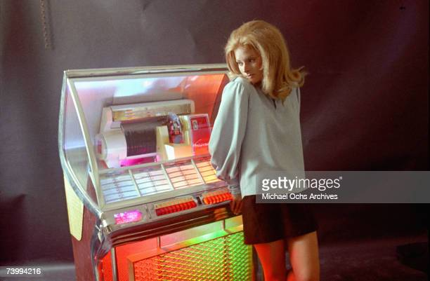 LATE 1960's A young woman stands in the glow of a multicolored Juke box in the late 1960's