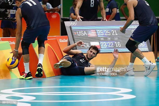USA's Aaron Russell is helped up by a teammate after diving for the ball during the men's quarterfinal volleyball match between USA and Poland at...