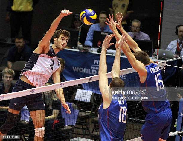 USA's Aaron Russell takes a shot against Russia's Alexander Volkov and Victor Poletaev during the first set of an FIVB World League match at Kay...