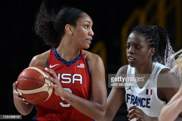 S A'ja Wilson handles the ball past France's Endene Miyem in the women's preliminary round group B basketball match between France and USA during the...