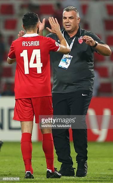 S Al-Ahli coach Aurelian Cosmin Olaroiu celebrates with Ossama Assaidi at the end of their AFC Champions League semi final football match against...
