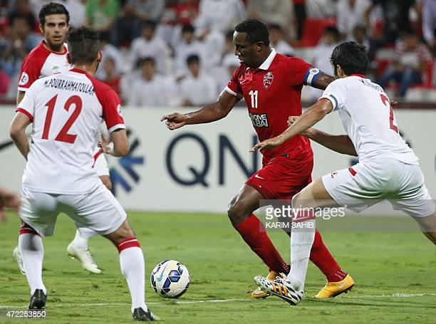 UAE's AlAhli FC Ahmed Khalil dribbles the ball in between Mohammad Pour Rahmatollah and Mohammed Iranpourian of Iran's Tractor Sazi club during their...