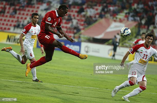 UAE's AlAhli FC Ahmed Khalil kicks the ball as Khaled Shafiei and Hani Hashemi of Iran's Tractor Sazi club watch on during their AFC Champions League...