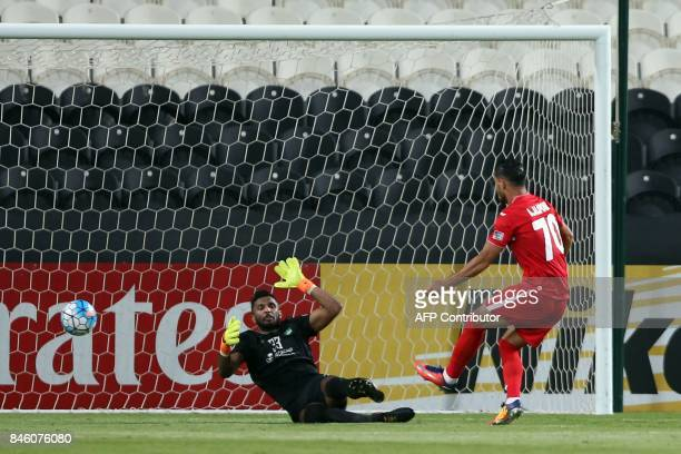 S Al-Ahli football team's Saudi goalkeeper Mohammed Khalil Al-Owais tries to defend a goal scored by Persepolis FC's Iranian player Ali Alipourghara...