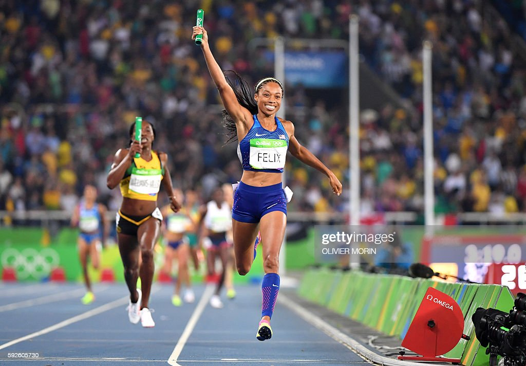 TOPSHOT - USA's Allyson Felix celebrates as she crosses the finish line to win the Women's 4x400m Relay Final during the athletics event at the Rio 2016 Olympic Games at the Olympic Stadium in Rio de Janeiro on August 20, 2016. / AFP / OLIVIER