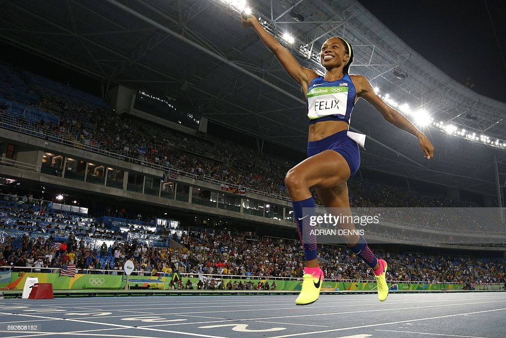 TOPSHOT - USA's Allyson Felix celebrates winning the Women's 4x400m Relay Final during the athletics event at the Rio 2016 Olympic Games at the Olympic Stadium in Rio de Janeiro on August 20, 2016. / AFP / Adrian DENNIS