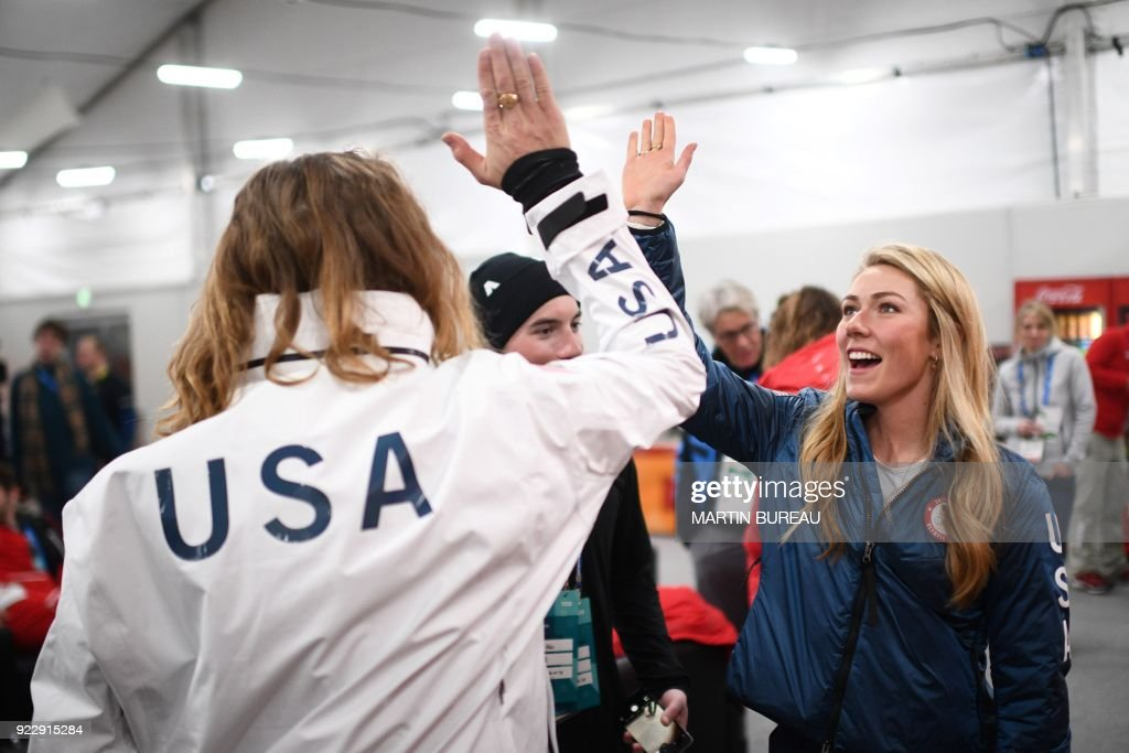 TOPSHOT - USA's alpine skiing medallist Mikaela Shiffrin (R) high fives USA's freestyle skiing halfpipe gold medallist David Wise backstage at the Athletes' Lounge during the medal ceremonies at the Pyeongchang Medals Plaza during the Pyeongchang 2018 Winter Olympic Games in Pyeongchang on February 22, 2018. / AFP PHOTO / Martin BUREAU