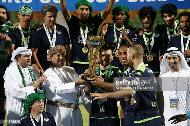 UAE's AlShabab club players are presented with the cup after winning the final of the GCC Champions League final football match against Oman's AlSeeb...