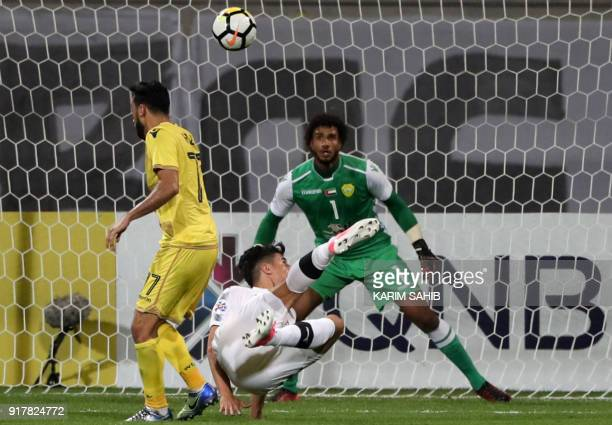 UAE's alWasl goalkeeper Sultan AlMenthri fails to save a shot on goal by Qatar's alSadd player Baghdad Bounedjah during the AFC Champions League...