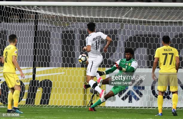 UAE's AlWasl goalkeeper Sultan AlMenthri fails to save shot on goal by Qatar's alSadd player Baghdad Bounedjah during the AFC Champions League group...