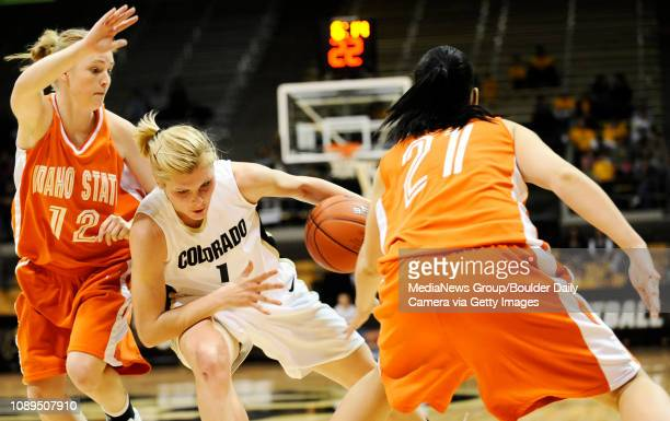 CU's Alyssa Fressle stumbles and travels the ball through Idaho State's Sheila Adams and Oana Iacovita during play at the Coors Event Center on the...