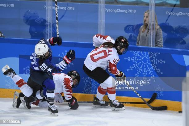 USA's Amanda Kessel and Canada's Meaghan Mikkelson collide as Canada's Blayre Turnbull controls the puck in the women's gold medal ice hockey match...