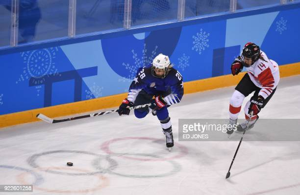 USA's Amanda Kessel and Canada's Renata Fast chase the puck in the women's gold medal ice hockey match between Canada and the US during the...