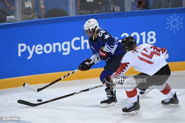 USA's Amanda Kessel and Canada's Renata Fast fight for the puck in the women's gold medal ice hockey match between the US and Canada during the...