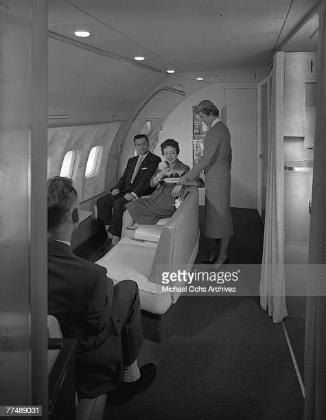 NEW YORK MID 1950's An air hostess serves passengers in the observation area of a Transocean Air lines Boeing 377 Stratocruiser in the mid 1950's...