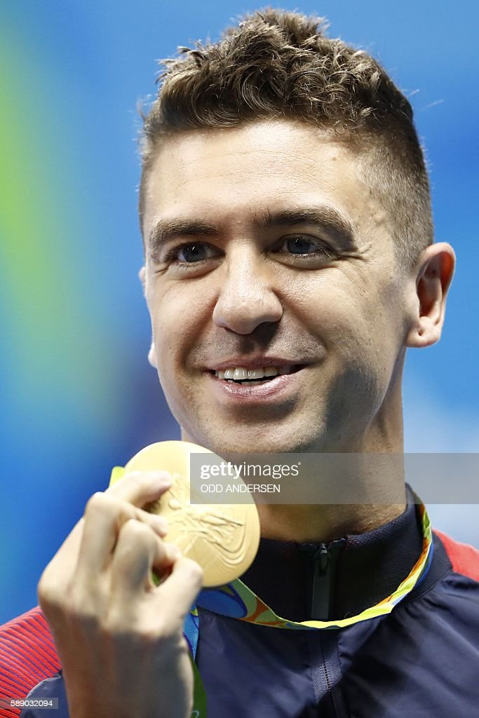 USA's Anthony Ervin celebrates with his gold medal after the Men's 50m Freestyle Final during the swimming event at the Rio 2016 Olympic Games at the Olympic Aquatics Stadium in Rio de Janeiro on August 12, 2016. / AFP / Odd Andersen