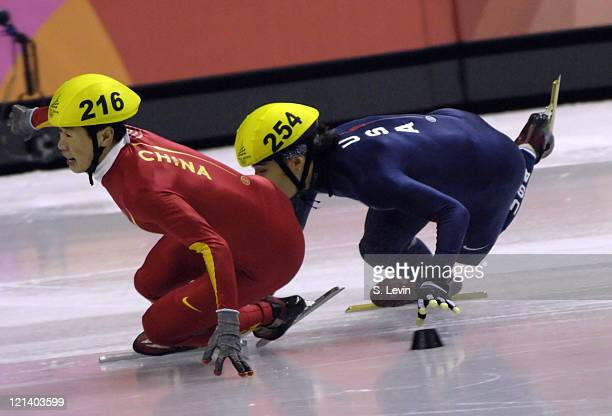 USA's Apolo Anton Ohno stumbles behind Ye Li of China in the Mens 1500 M Short Track event at the Palavela venue in Torino Italy on February 12 2006