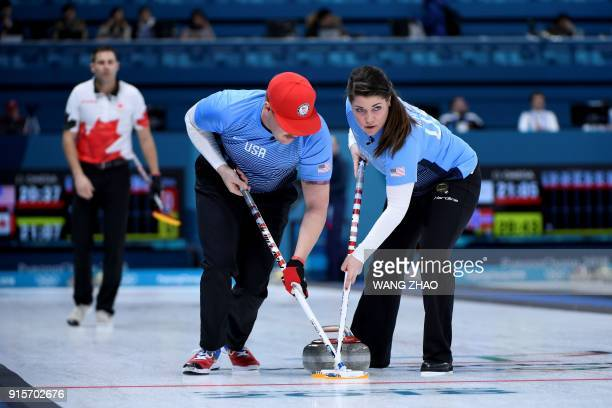 USA's Becca Hamilton and Matt Hamilton brush the ice surface during the curling mixed doubles round robin session between the US and Canada during...