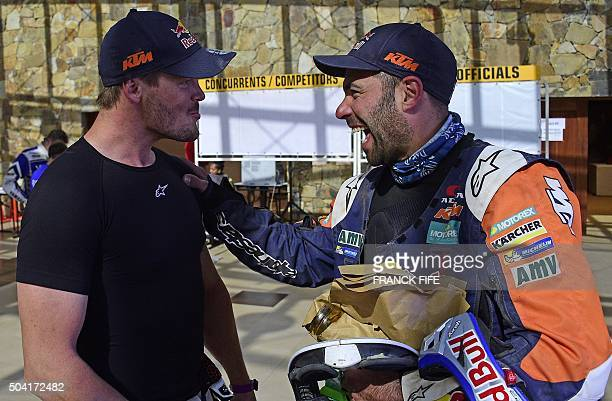 KTM's biker Antoine Meo of France is congratulated by KTM's Australian Toby Price in the bivouac after winning the Stage 7 of the Dakar 2016 between...
