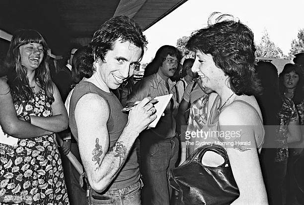 AC/DC's Bon Scott signs an autograph for a fan as the band returns to Sydney after an overseas tour 26 November 1976 SMH NEWS Picture by TON LINSEN