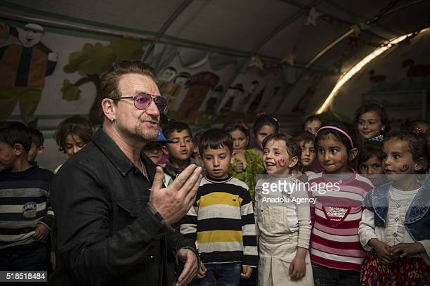 U2's Bono performs for the kids during a visit to a preschool at a tent city of Syrian refugees in Nizip district of Turkey's Gaziantep province on...