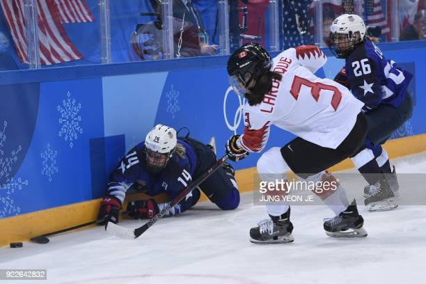 USA's Brianna Decker fights for the puck with Canada's Jocelyne Larocque in the women's gold medal ice hockey match between the US and Canada during...
