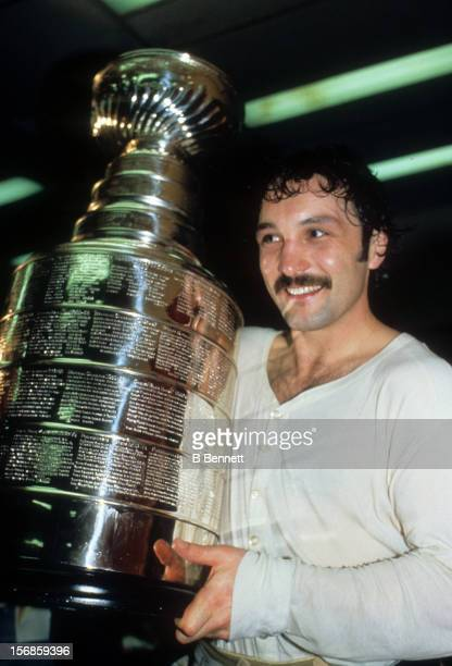 1980's Bryan Trottier of the New York Islanders smiles while he holds the Stanley Cup Trophy after one of the Islanders Stanley Cup victories in the...