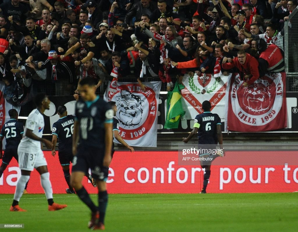 LOSC's Cameronian midfielder Ibrahim Amadou (R) celebrates with supporters after LOSC's French defender Fode Ballo-Toure (L) scored a goal during the French L1 football match between Amiens and Lille LOSC on September 30, 2017 at the Licorne stadium in Amiens. /