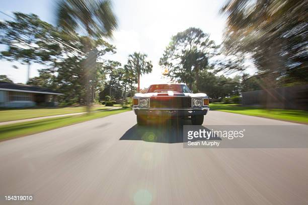 1970's car driving on a street - 1970s muscle cars stock pictures, royalty-free photos & images