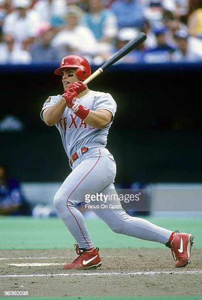 CIRCA 1990's Catcher Ivan Rodriguez of the Texas Rangers swings and watches the flight of his ball during a circa mid 1990 Major League Baseball game...