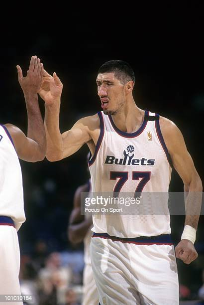 S: Center Gheorghe Muresan of the Washington Bullets in this portrait giving a teammate a high-five circa mid 1990's during an NBA basketball game at...