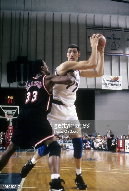 BALTIMORE MD CIRCA 1990's Center Gheorghe Muresan of the Washington Bullets is guarded closely by center Alonzo Mourning of the Miami Heat circa mid...