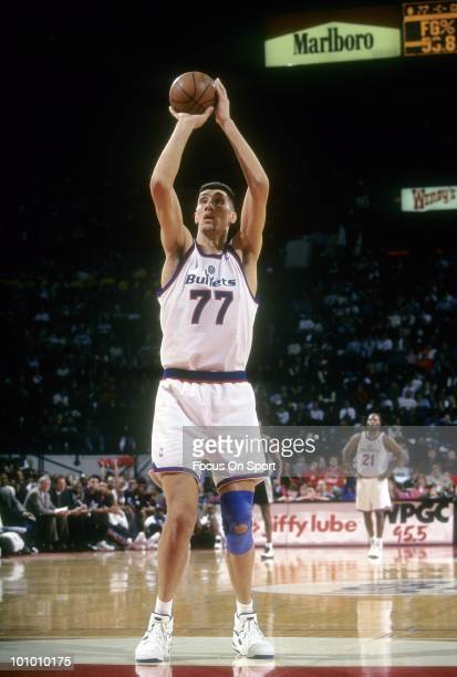 S: Center Gheorghe Muresan of the Washington Bullets shoots a free throw against the San Antonio Spurs circa mid 1990's during an NBA basketball game...