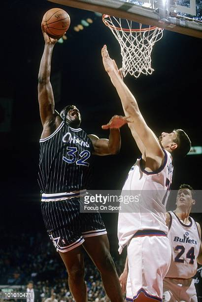 BALTIMORE MD CIRCA 1990's Center Shaquille O'Neal of the Orlando Magic shoots over Gheorghe Muresan of the Washington Bullets circa mid 1990's during...