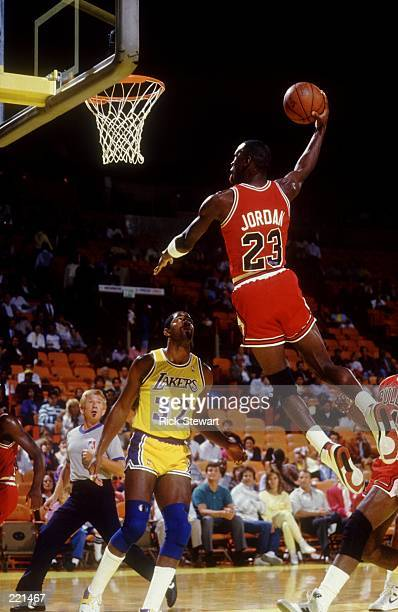 1980's CHICAGO GUARD MICHAEL JORDAN FLIES TO THE BASKET FOR A DUNK OVER LOS ANGELES GUARD MAGIC JOHNSON DURING THE BULLS GAME VERSUS THE BULLS AT THE...