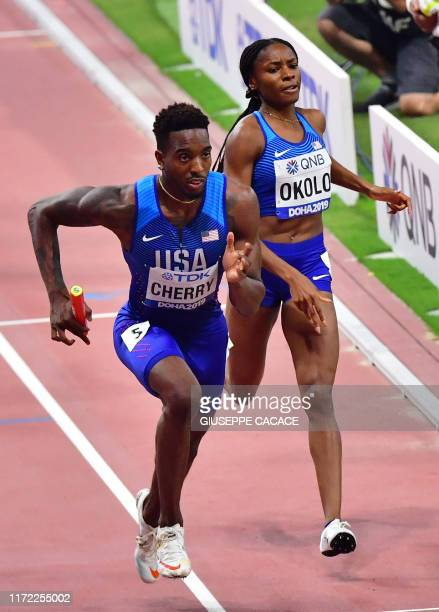 USA's Courtney Okolo passes the baton to USA's Michael Cherry in the Mixed 4 x 400m Relay final at the 2019 IAAF World Athletics Championships at the...