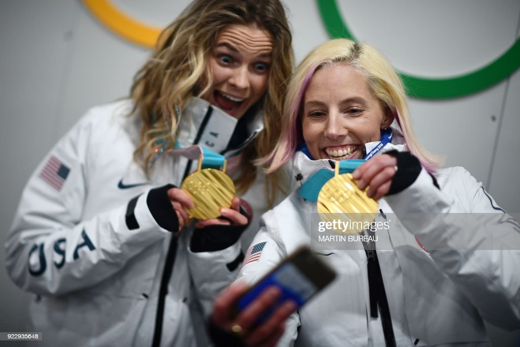 TOPSHOT - USA's cross country team sprint gold medallists Kikkan Randall and Jessica Diggins pose for a selfie backstage at the Athletes' Lounge during the medal ceremonies at the Pyeongchang Medals Plaza during the Pyeongchang 2018 Winter Olympic Games in Pyeongchang on February 22, 2018. / AFP PHOTO / Martin BUREAU