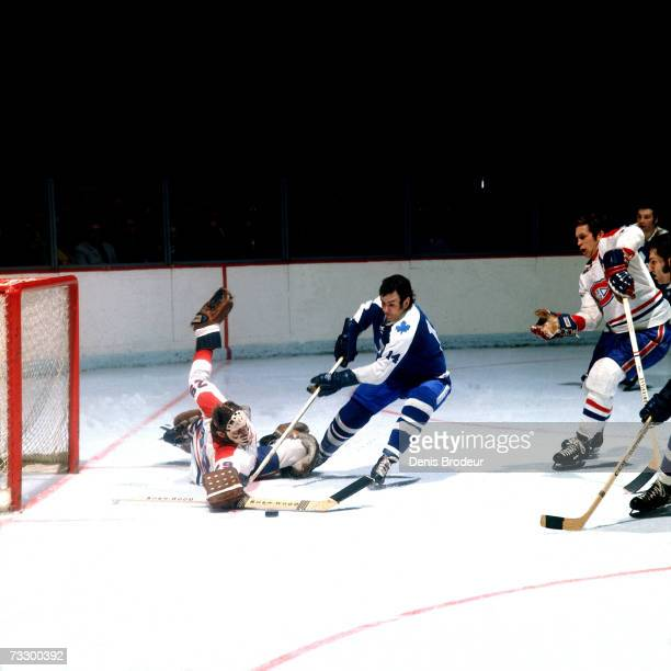 Dave Keon of the Toronto Maple Leafs skates for the puck against Ken Dryden of the Montreal Canadiens.
