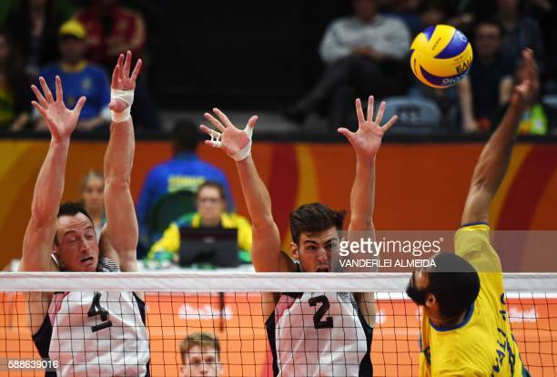 USA's David Lee and Aaron Russell jump to block the ball during the men's qualifying volleyball match between Brazil and the USA at the Maracanazinho...