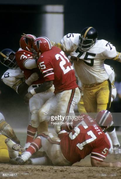 ATLANTA GA CIRCA 1970's Defensive lineman Joe Greene of the Pittsburgh Steelers assist teammate LC Greenwood in bringing down the Atlanta Falcons...